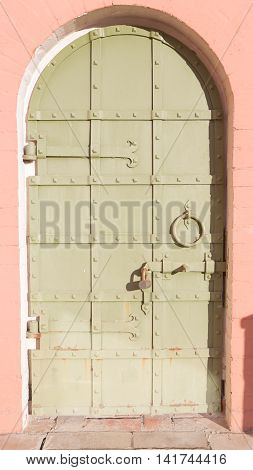 Green rough old arched door with protrusions in the form of rivets and metal strips bolted in a bright red wall plastered