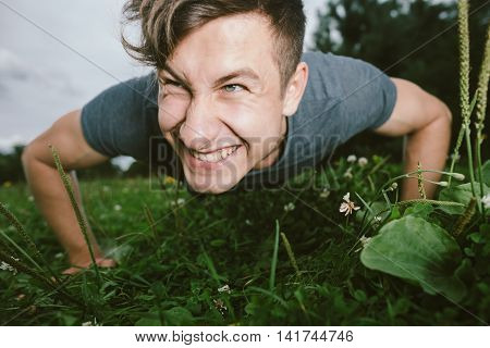 Smiling young man doing push-ups outdoors .