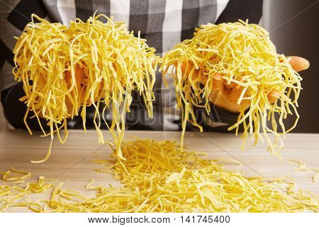 Home made pasta,  italian spaghetti, women making dough on table - preparing lunch