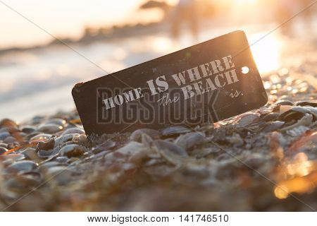 Home is where the beach is. Tag with the inscription on the shore of the sea and sunset background