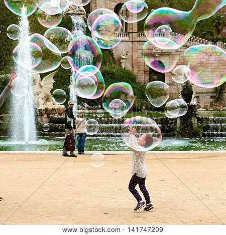 Barcelona Spain - April 4 2016: Little girl catching the soap bubbles in the in the Ciutadella Park in Barcelona. Ciutadella park is one of the finest parks in Barcelona. Park dotted with historic landmarks statues and fountains