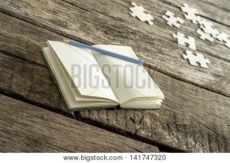 Blank white book with pencil and puzzle pieces over old weathered wooden table for theme about memories and introspection.
