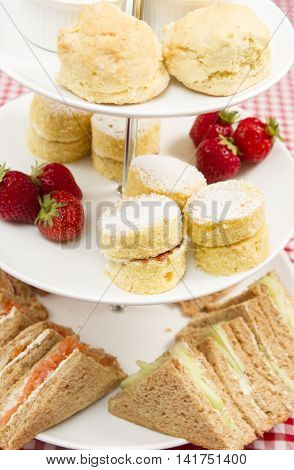 Traditional British afternoon tea A cake stand containing various cakes and sandwiches as part of a traditional British afternoon tea