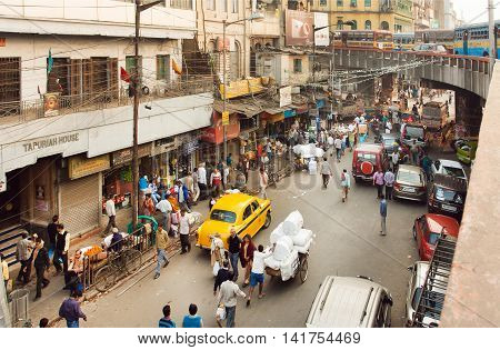 KOLKATA, INDIA - JAN 18, 2016: Street movement with cars trader trolleys and crowd of people in huge asian city on January 18, 2016. Kolkata has a density of 814.80 vehicles per km road length