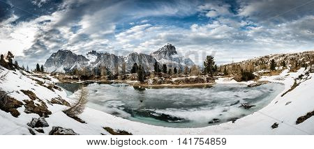 Winter mountain landscape with frozen lake in the front and dramatic sky above. Wilderness raw nature concept and background. Lago Limides Dolomites.
