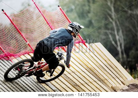 athlete man extreme cyclist riding Insloped Turn during competitions in downhill