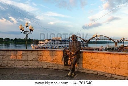 RYBINSK RUSSIA - JULY 21 2016: Unidentified people walk in open air near monument to Lev Oshanin on waterfront of Rybinsk at sunset