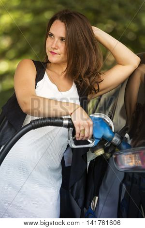 brunette woman at gas station refuelling her car