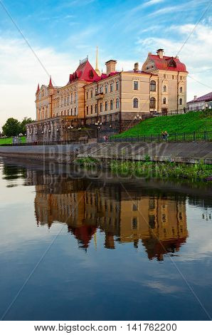 RYBINSK RUSSIA - JULY 21 2016: Unidentified people walk on promenade near old building of Rybinsk State Historical-Architectural and Art Museum-Reserve (former Grain Exchange) in evening Russia