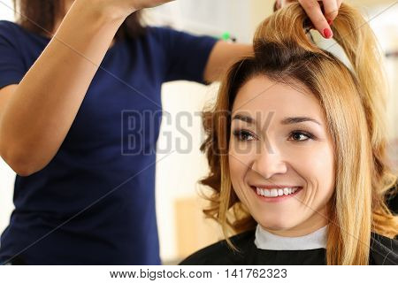 Female hairdresser hold in hand between fingers lock of hair of blonde beautiful visitor. Keratin restoration latest trend fresh idea haircut picking shorten tips instrument store concept