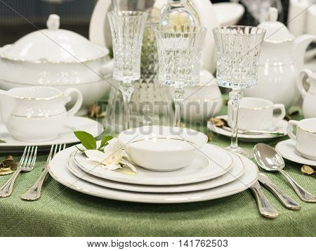 Set of new dishes on table with green tablecloth. Stack of white plates with flowers on restaurant table. Shallow DOF