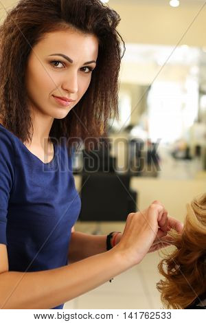 Portrait of beautiful smiling brunette hairdresser hold in hands lock of blonde blonde hair. Keratin restoration latest trend fresh idea haircut picking shorten tips instrument store concept