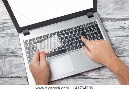 Hands holding business credit card typing numbers on laptop computer keyboard making online payment at home against grunge black and white wooden desk table On-line shopping concept. Selective focus