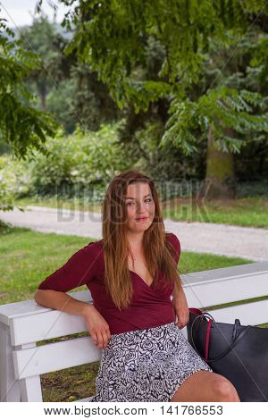Young beautiful girl sit on a banch with handbag