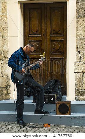Lviv Ukraine - September 21 2014: Man playing guitar for citizens in the old quarter of the city of Lviv Ukraine.