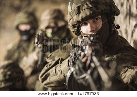 Closer shot of a young soldier in helmet standing with the weapon and with two other soldiers behind him