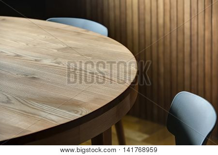 Two gray chairs near the round wooden table on the background of the wooden wall. On the floor there is a parquet. Indoors. Horizontal.