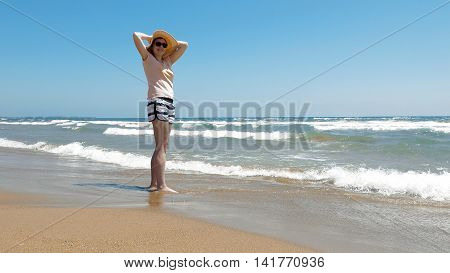 A woman is standing at the beach with her jute hat on. Jute hats are really popular in fashion industry. She is enjoying the sunny day with fresh breeze.