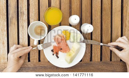 The lady sitting at the wooden table is devouring a plate with meals. The lady is using cutlery utensils to cut her fruit dish meal in small bites. Top view. Unusual POV.