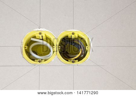 Two yellow electrical sockets installed in drywall