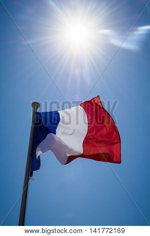 French flag shot against strong sunshine along stretch of the French Riviera