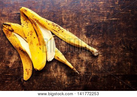 Ripe bananas peel on vintage wooden background. Over ripe peeled banana close up