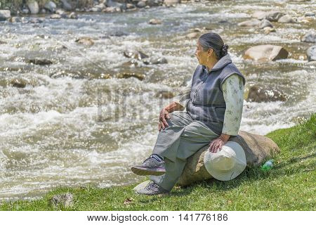CUENCA, ECUADOR, NOVEMBER - 2015 - Senior woman sitting at rock enjoying the day at park in front of river in Cuenca Ecuador