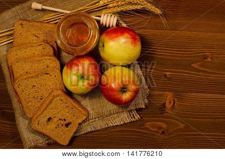 Three apples slices of rye bread honey wheat ears on sacking wooden table