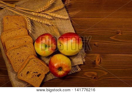 Slices of rye bread three apples ears of wheat on sacking wooden table top view