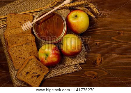 Jar of honey apples rye bread ears on sacking wooden table top view