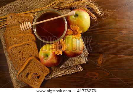 Jar with honey rye bread apples yellow daisy and ears on sacking wooden table top view