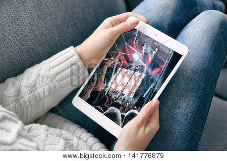 Female hand holding PC tablet on home interior background. Spotlight with laser rays on screen