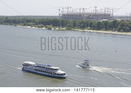 Rostov-on-Don Russia -August 062016: Vessels with passengers on board flow along Don River past the Olympic stadium being constructed