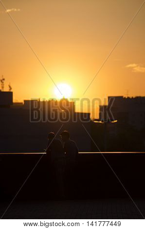 Two men are talking in sunset lights