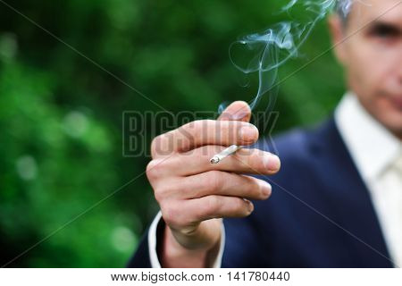 A gentleman smokes a cigarette. The man with the cigarette smoke in the lung. The smoke from the cigarette in his hands. Smoking is fine.