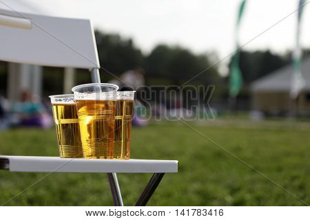 Three plastic glasses of beer on chair in park