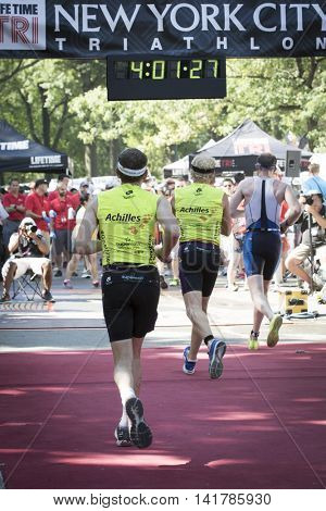 NEW YORK CITY -  JULY 24 2016: Achilles International athletes cross the finish line of the NYC Triathlon Race in Central Park. The run is 10k and the race is the only International Distance triathlon in NYC.