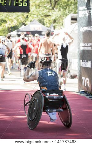 NEW YORK CITY -  JULY 24 2016: ParaTriathlete from CAF, Challenged Athletes Foundation, crosses the finish line in Central Park in the NYC Triathlon Race, the only International Distance triathlon in the city.