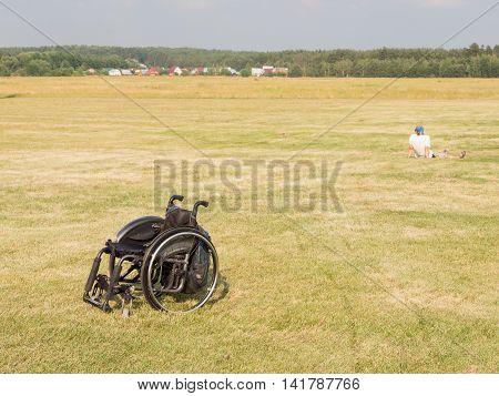 The Moscow region - 15 July 2016: Black wheelchair standing in a field on festevale