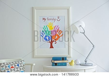 Family hand prints in frame hanging on wall in room