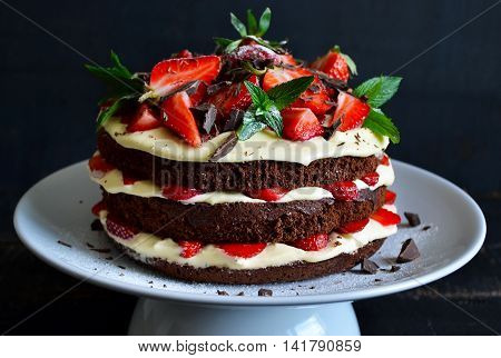 Naked cake with cream decorated with strawberry mint and chocolate on a black background