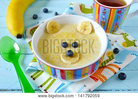 Kids breakfast porridge with fruits and berries face bears