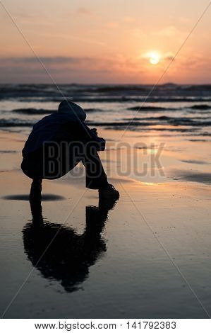 Cape Lookout, Oregon, USA - July 14, 2009 : man silhouette sit on the beach taking picture at sunset in Cape Lookout Oregon