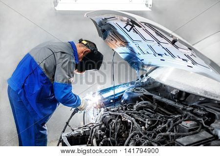 professional repairman worker in automotive industry welding metal body car with sparks.