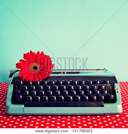 Vintage turquoise typewriter with a red flower
