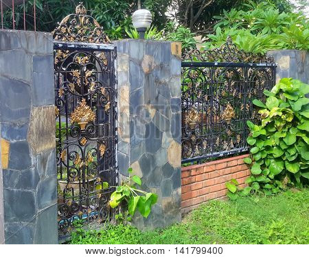 faux gray and brown stone wall pillars with brick base and scrolled black and gold wrought iron fence above, with small scrolled gate in foreground, seen from the street in Songkhla, Thailand