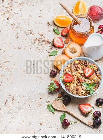 Healthy breakfast ingredients. Oat granola in bowl with nuts, strawberry and mint leaves, pitcher, honey, fresh fruits and berries on light concrete background, top view, selective focus, copy space, vertical composition