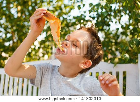 boy eating pizza. child closed his eyes in pleasure and takes a bite of pizza piece holding it aloft