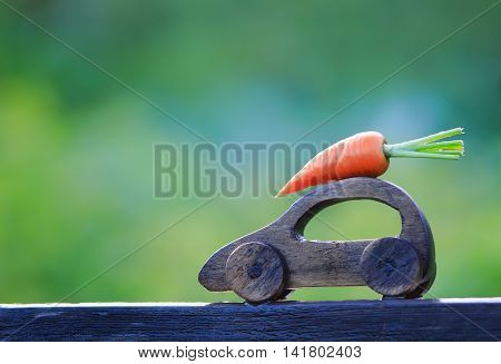 toy wooden car carries the carrot on the roof. harvest. the concept of organic vegetables from the farm. empty space for your text