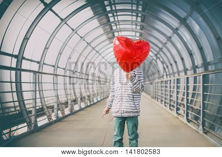 boy in dark tunnel with red heart in the hands. teen hid his face behind a red balloon in the shape of a heart. the concept of first love